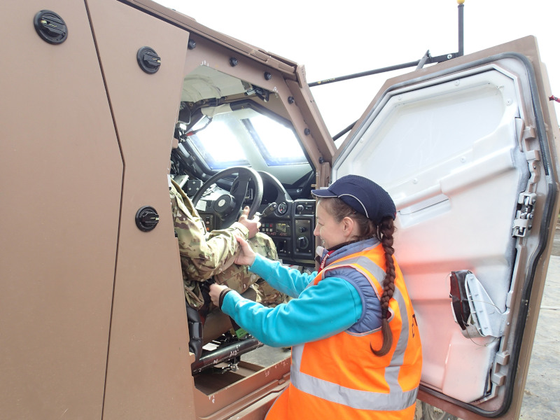 Dr Melanie Franklyn making final adjustments to an anthropomorphic test device seated inside a Hawkei vehicle in preparation for a blast test.