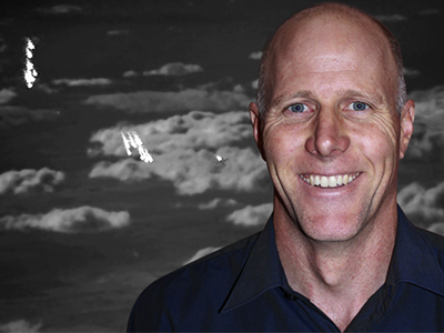 A VIRSuite generated scene for air-to-air missile testing with an aircraft dispensing flares in front of a cloud background. Shawn Garner, pictured inset.