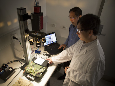 DST scientists Jay Yu (foreground) and Bin Lee using a benchtop hyperspectral imaging camera to conduct material reflectance property measurements.