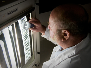 A scientist examines an x-ray image of materials affected by structural fatigue.