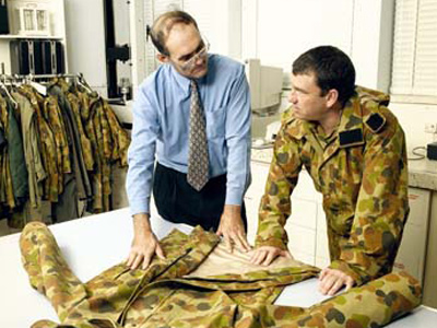 Graeme Egglestone (left) inspects a camouflage jacket with a soldier.