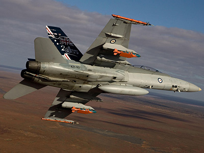 A Royal Australian Air Force F/A-18 Hornet in flight with two JDAM-ER 500lb bombs and two Time Space Position Information pods.