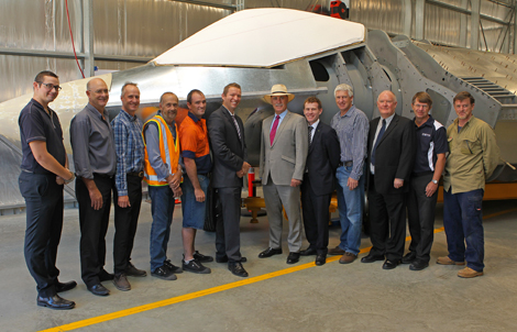 A photograph of the Minister for Defence Science and Personnel standing with DSTO personnel in front of the model of the Joint Strike Fighter.