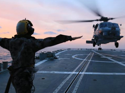 Image of a soldier signalling to a helicopter.