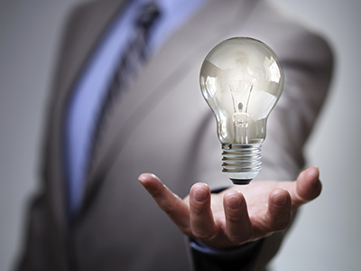 The torso of a man in a suit, holding up a lightbulb.