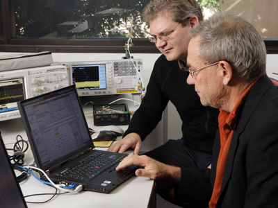Two men working on a laptop computer.