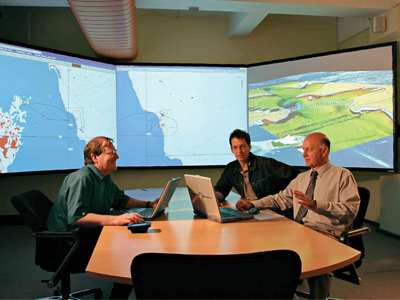 An image of three men at the Concept Exploration and Analysis Laboratory CEAL at DST Group in Sydney, discussing naval technology