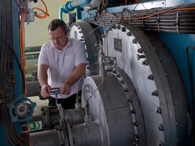 An image of a man working on a compressor in the Combustion Test Facility