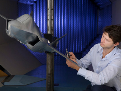 Photo of a staff member working on a model of the JSF aircraft in the Transonic Wind Tunnel.