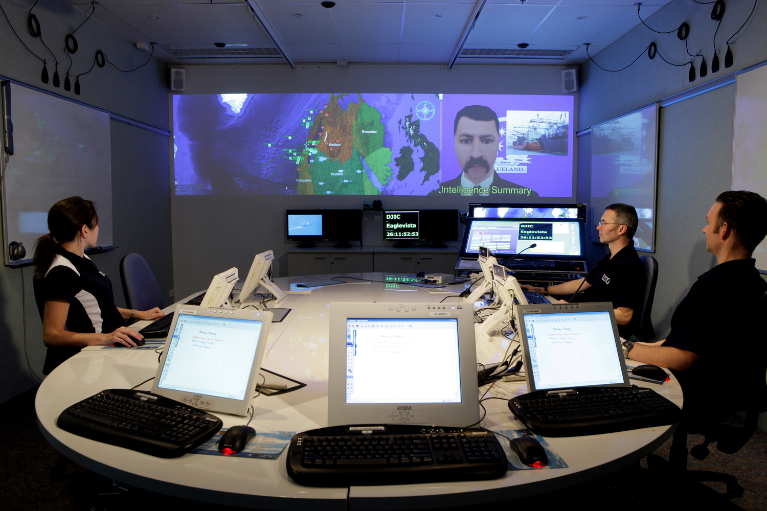 DSTO's Intense Collaboration Space laboratory is controlled by the DSTO-developed and now open-sources Livespaces Operating System for distributed collaboration within smart meeting room environments. On the projected screens a Virtual Adviser (right) is briefing meeting participants on a military scenario with the aid of a Virtual Battlespace (left). The Virtual Adviser and Virtual Battlespace software were also developed by DSTO.