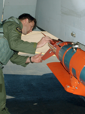 An image of a pilot inspecting a glide bomb.