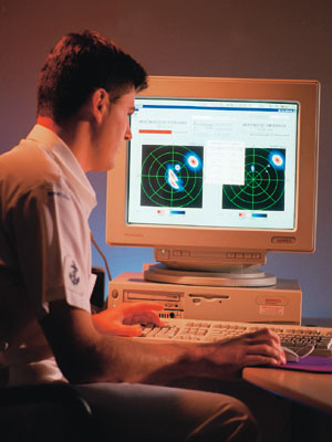 A photograph of a man looking at a computer screen displaying MEXANS software