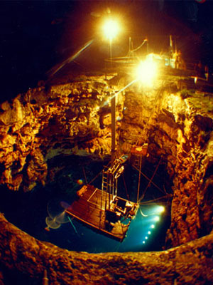 A photograph of barra sonobuoy being tested at night, under lights in a large hole.