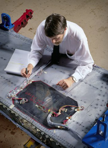 Dr. Richard Chester examines a composite bonded repair to an F-111 wing.