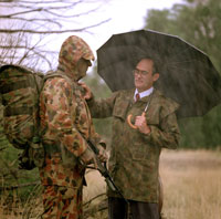 A photo of Graeme Eggleston assessing raingear on a soldier in the rain