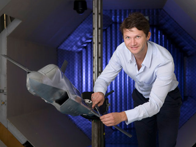 DST scientist in the Low Speed Wind Tunnel with a model plane.