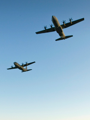 Two C-130J aircrafts fly overhead.