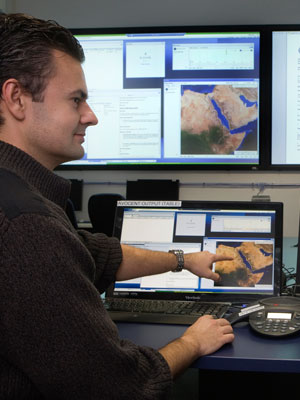 Two DST Group researchers working in front of several computer screens.
