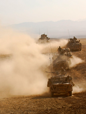 A convoy of land vehicles drive across a desert.