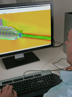 An image of a man looking at a computer image of a submarine.