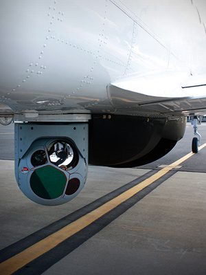 An aircraft with surveillance cameras mounted below it.
