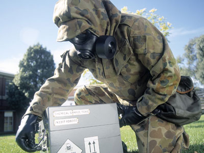 An image of a person wearing protective clothing handling a box containing hazardous materials.