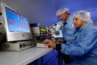 Two DST Group scientists conduct laser micro machining.