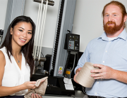 Vanessa Ha and Mark Ryan with the equipment used to stretch the yarn samples used in their shape-memory polymer research.