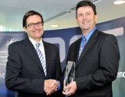 Greg Combet shaking hands with Dr Gordon Frazer after presenting him with his award.
