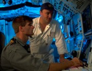 Submarine officers review an undersea computer system.