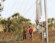 An image of two scientists in the outback examining a radar technology rig.