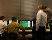 Defence members gathered around computers at a Defence wargame facility