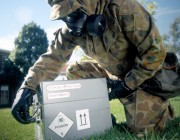 An officer, wearing protective material, examines a hazardous box as part of a safety demonstration.