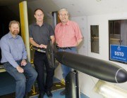 Three scientists with a submarine model in DST's Low Speed Wind Tunnel.