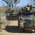A soldier (left) alongside a bushmaster vehicle.