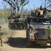 A soldier (left) alongside a bushmaster vehicle.