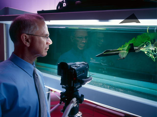 DST Group scientist Lincoln Erm studying the flow over a modern combat aircraft in the Water Tunnel.
